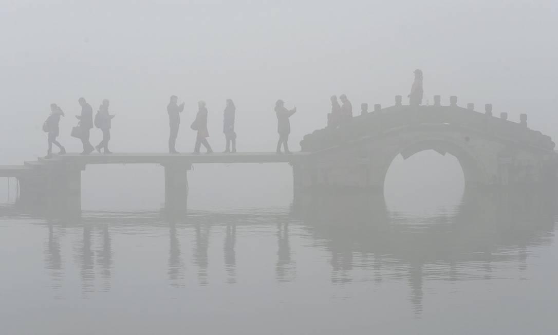 Visitantes caminham por uma ponte às margens do Xī Hú (Lago Oeste), lago de água doce, envolta em denso smog em Hangzhou, na província de Zhejiang, na China, em 8 de dezembro de 2015 CHINA DAILY / REUTERS
