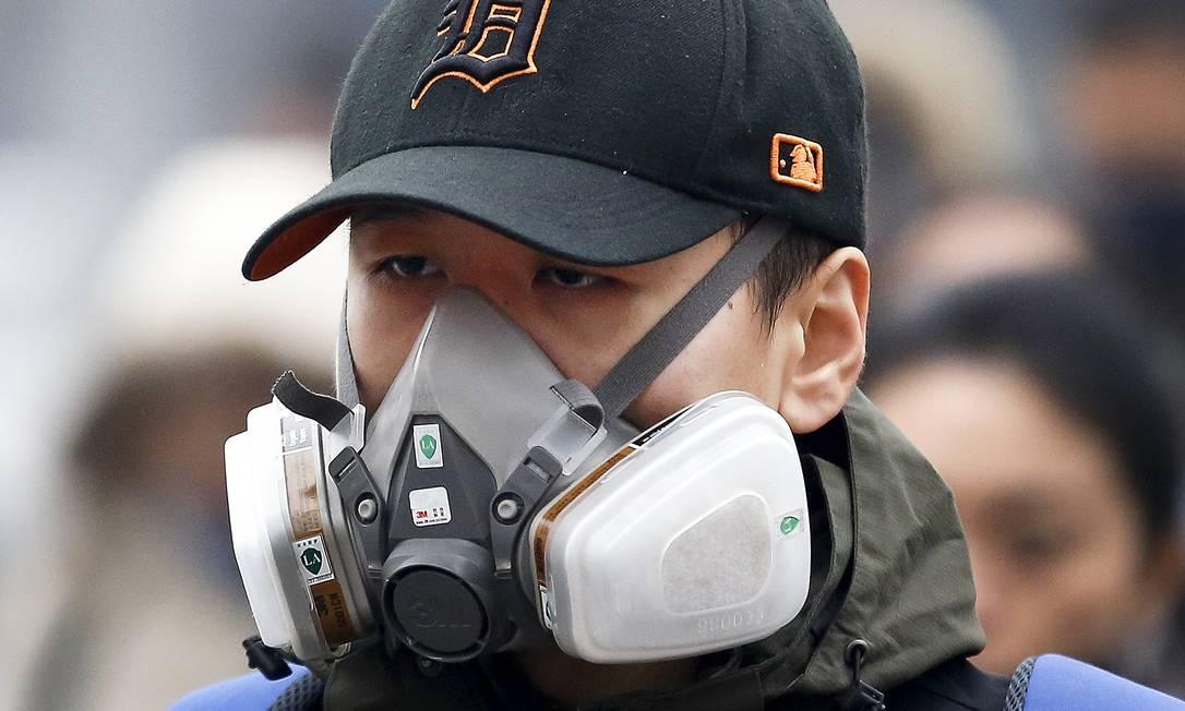 Um homem usa máscara antipoluição em Pequim, cidade em que episódios de smog duram diversos dias durante o inverno Andy Wong / AP