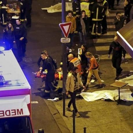 Bombeiros resgatam um ferido próximo à casa de espetáculos Bataclan Foto: Christian Hartmann / Reuters