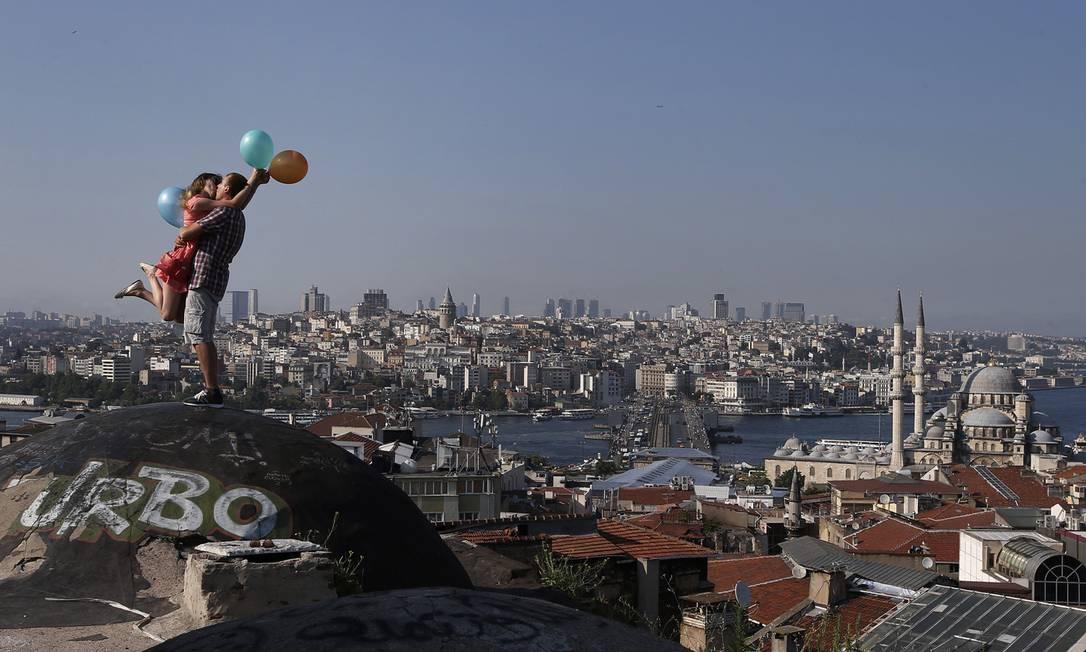 Outro casal de desconhecidos, outro beijo mágico. Agora com Istambul, na Turquia, ao fundo Emrah Gurel / Emrah Gurel/AP