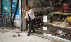 Marieta Almeida varre a fachada da loja: queda do movimento. Foto: Hermes de Paula / Agência O Globo