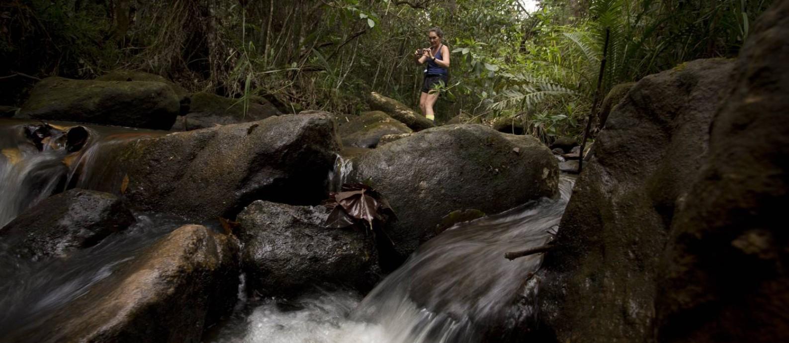 Mulher fotografa córrego que deságua no Rio Gualaxo do Norte: águas transparentes perto de toda a destruição causada pela tragédia da Samarco Foto: Marcia Foletto/27-11-2015