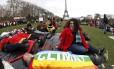 """Membros de ONGs se deitam nos jardins da Torre Eiffel, em Paris, para chamar atenção para as consequências das mudanças climáticas. Um homem cobre o corpo com uma bandeira multicolorida na qual pode se ler a palavra """"clima"""", em francês"""