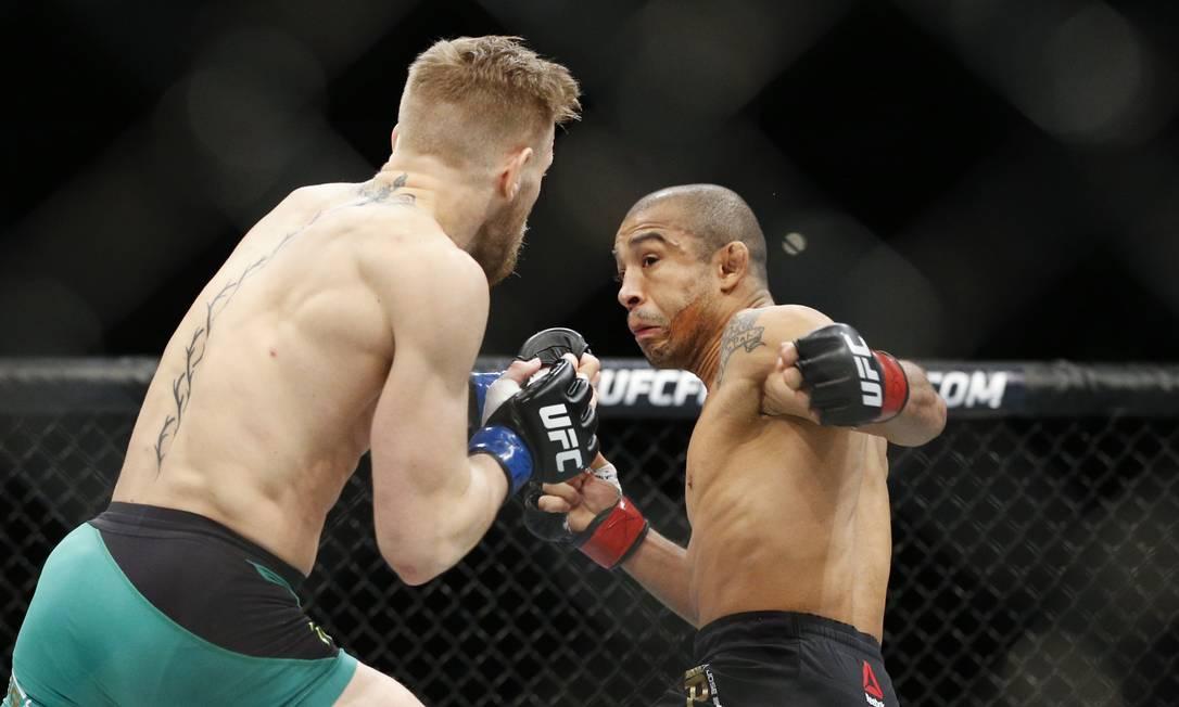 Frações de segundo antes de ser atingido pela bomba de canhota de Conor McGregor, José Aldo tenta o cruzado de esquerda no adversário: primeira derrota do brasileiro em dez anos no MMA John Locher / AP