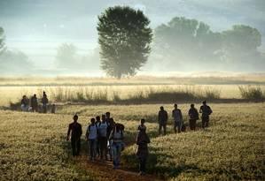 Imigrantes atravessam campo para cruzar a fronteira entre a Grécia e a Macedônia Foto: ARIS MESSINIS / AFP