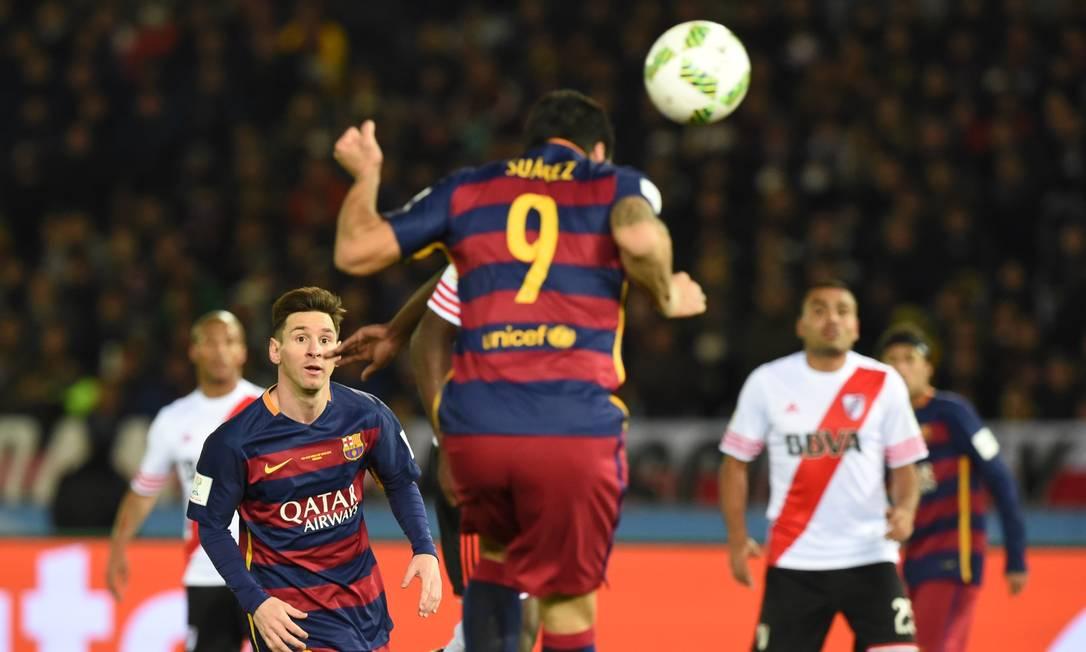 Observado por Messi, Luís Suárez cabeceia para marcar o terceiro gol TOSHIFUMI KITAMURA / AFP
