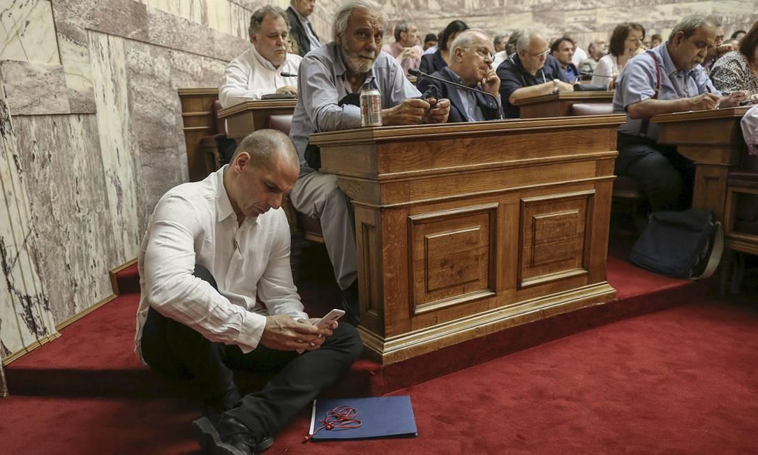 O então ministro das Finanças grego, Yanis Varoufakis, mexe no celular durante as extenuantes horas de negociações no Parlamento sobre a dívida Foto: COSTAS BALTAS / REUTERS