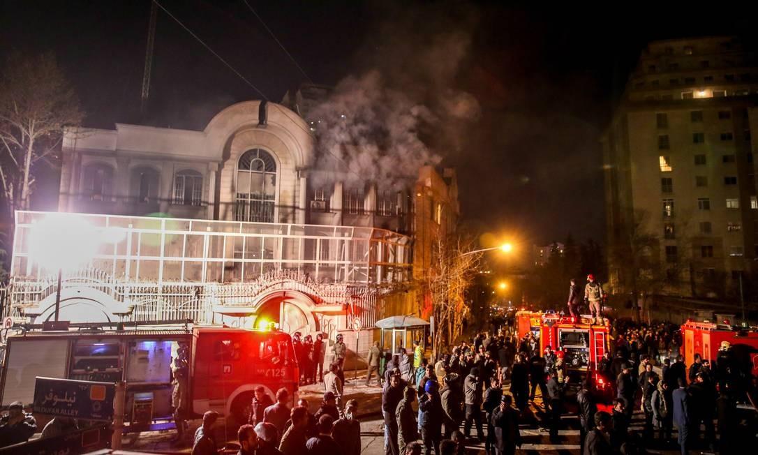 Bombeiros combatem o fogo ateado em anexo da embaixada da Arábia Saudita em Teerã enquanto policiais se ocupam em dispersar os manifestantes Foto: ATTA KENARE / AFP/ATTA KENARE