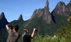 Visitantes tiram fotos em mirante em frente ao pico Dedo de Deus, em Teresópolis. A força do turismo ajudou na recuperção da imagem da região serrana. Foto: Custodio Coimbra / O Globo