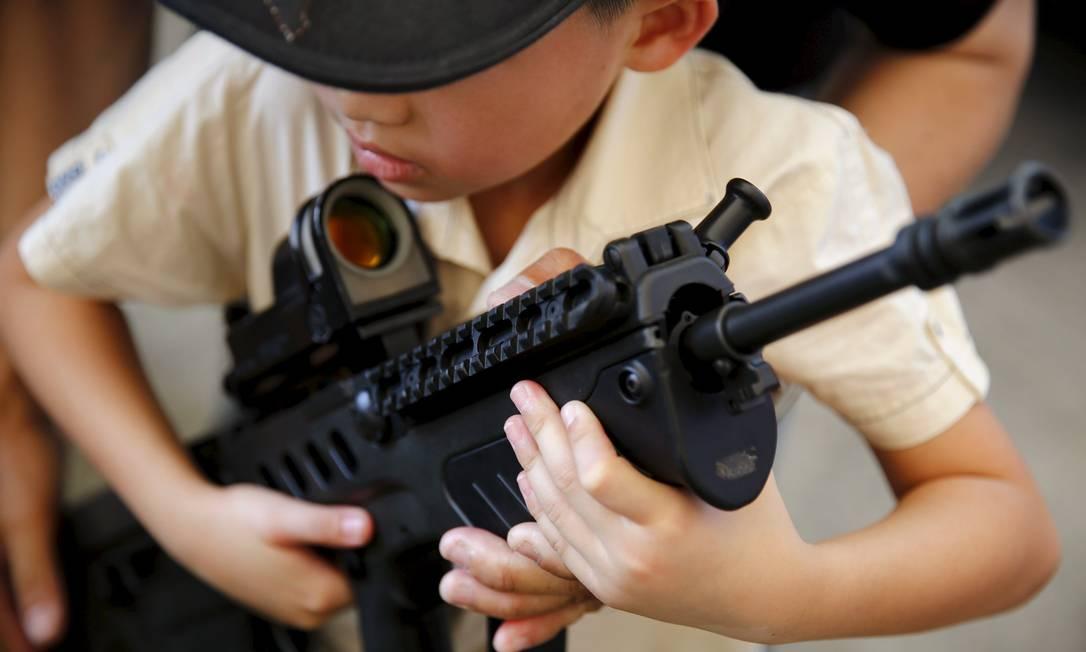 Menino carrega uma arma durante a comemoração do Dia da Criança em uma instalação militar em Bangkok, na Tailândia JORGE SILVA / REUTERS