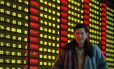 Homem passa em frente a painel eletrônico com o desempenho das ações chineses