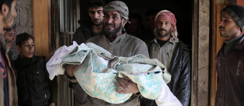 Pai carrega o corpo de uma menina síria de dez anos, morta por ataques aéreos que atingiram um jardim de infância, na aldeia de Deir al-Asafir, região controlada pelos rebeldes nos arredores de Damasco Foto: AMER ALMOHIBANY / AFP