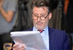 Sebastian Coe lê o relatório com acusações de que ele sabia do esquema de doping Foto: Kerstin Joensson / AP