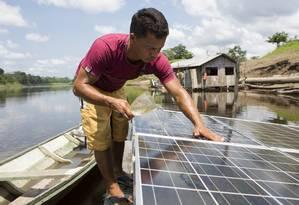 Morador de Vila Várzea Alegre, no Amazonas, limpa os painéis que ajudam a bombear água para casa, evitando que ele tenha que descer ao rio várias vezes ao dia Foto: Otávio Almeida/Greenpeace