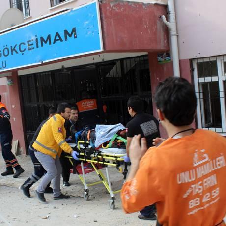 Membros do serviço de emergência retiram um homem ferido após escola ser atingida por projétil na Turquia Foto: STRINGER / AFP