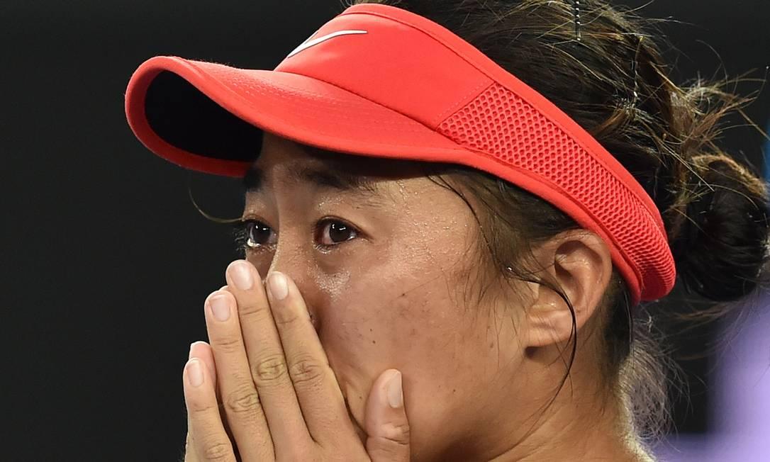 A chinesa Zhang Shuai se emociona após derrotar a romena Simona Halep na primeira rodada SAEED KHAN / AFP