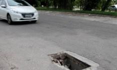 Bueiro sem tampa na Curva Chico Anysio em frente à Vila do Pan: perigo a motoristas Foto: Fernanda Dias / Agência O Globo