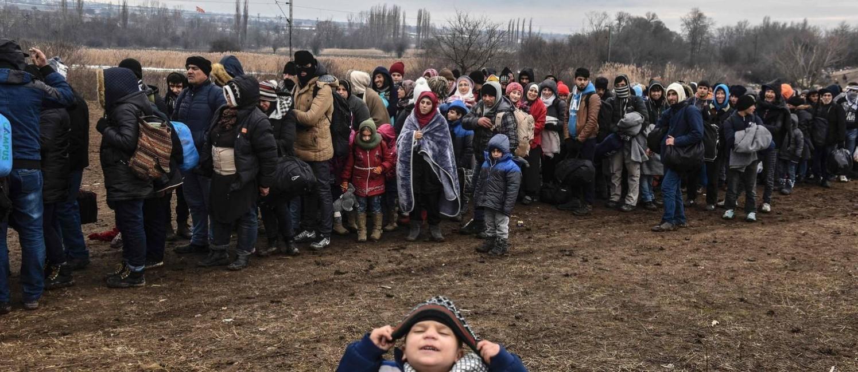 Saga nos Bálcãs. Criança refugiada brinca diante da câmera enquanto parentes esperam na fila de imigração na fronteira entre Macedônia e Sérvia: países da UE querem estender período de exclusão da zona de livre circulação Foto: ARMEND NIMANI/AFP