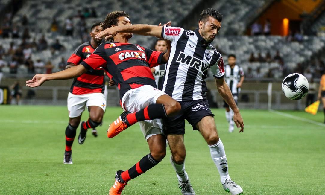 Willian Arão, do Flamengo, disputa a bola com Dátolo, do Atlético-MG Divulgação