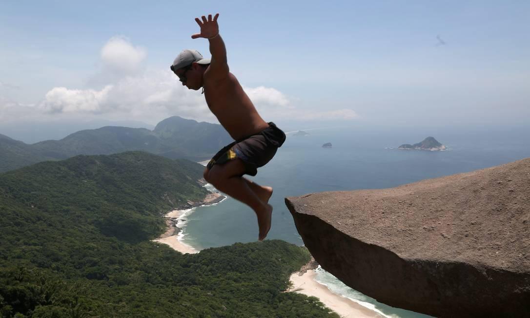 Rafael Dias, de 22 anos, foi mais ousado: pulou da pedra, mesmo com risco de acidente. Vale tudo por uma foto nunca postada antes no Instagram Foto: Custódio Coimbra / Agência O Globo