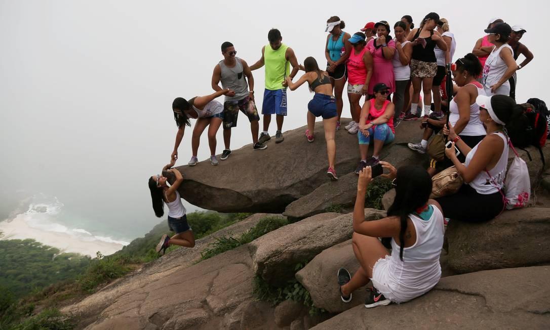 A fila sobre a pedra para a foto: enquanto jovem tenta se pendurar na rocha, outros esperam o seu minuto de fama no Instagram Foto: Custódio Coimbra / Agência O Globo