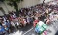 Foliões ficam contra o muro durante o desfile do bloco Me Esquec
