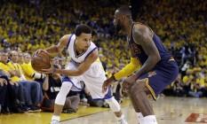Stephen Curry segura a bola, marcado por LeBron James Foto: Ben Margot / AP