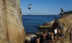 Diante de uma plateia, jovem pula de pedra junto à Cláudio Coutinho Foto: Daniel Marenco / O Globo