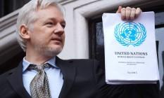 Julian Assange aparece na sacada da embaixada do Equador em Londres exibindo o inquérito da ONU que considerou sua detenção ilegal Foto: NIKLAS HALLE'N / AFP