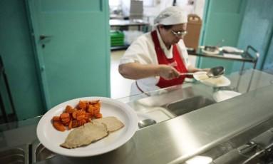 Merendeira prepara refeição em escola de Corsico Foto: ALESSANDRO GRASSANI / NYT