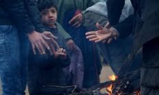 Criança se aquece em fogueira ao lado de refugiados em Idomeni, na fronteira entre a Grécia e a Macedônia Foto: SAKIS MITROLIDIS / AFP