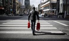 Homem atravessa uma rua com compras na China. Foto: Qilai Shen/Bloomberg
