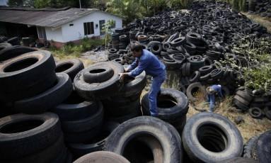 Agentes de saúde buscam focos de mosquito em depósito em Villavicencio, na Colômbia Foto: Fernando Vergara / AP
