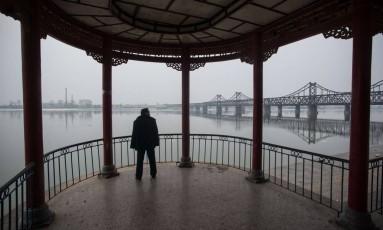 Homem faz exercícios em frente ao rio Yalu, que separa a China da Coreia do Norte Foto: JOHANNES EISELE / AFP