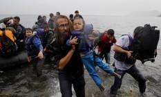 Voluntário resgata criança síria após chegar na ilha grega de Lesbos Foto: YANNIS BEHRAKIS / REUTERS