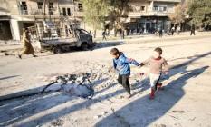 Meninos correm perto de local atingido por ataque do regime sírio perto de Aleppo Foto: ABDALRHMAN ISMAIL / REUTERS