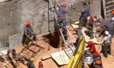 Bombeiros trabalham com o auxílio de retroescavadeira Foto: Reprodução TV Globo