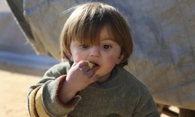 Um garoto sírio aguarda em um campo de refugiados na fronteira com a Turquia após fugir de intensos confrontos na região de Aleppo Foto: AP