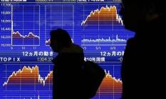 Oscilação. Pedestres passam em frente a um painel eletrônico que mostra gráficos sobre as recentes flutuações da Bolsa do Japão, em Tóquio Foto: YUYA SHINO / Yuya Shino/Reuters