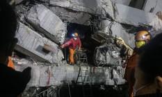 Equipe de resgate procura por sobreviventes nos escombros de prédio que desabou em Taiwan Foto: ANTHONY WALLACE / AFP