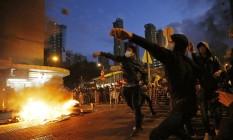 Manifestantes jogam pedras na polícia que tentava retirar barracas de vendedores ilegais em Hong Kong Foto: Kin Cheung / AP