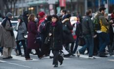 Trabalhadores atravessam a rua em Washington ao fim de um dia de trabalho Foto: Andrew Caballero-Reynolds/AFP
