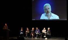 Com participação por vídeo de Julian Assange, o 'popstar' Yanis Varoufakis (esquerda) lidera debate em teatro berlinense Foto: TOBIAS SCHWARZ / AFP