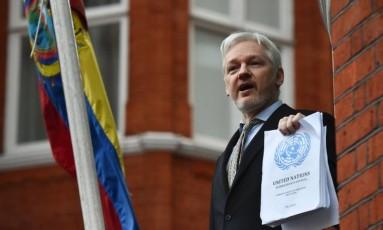 Assange mostra documento da ONU que declara irregularidades do Reino Unido no processo de detém o ativista na embaixada equatoriana Foto: Ben Stansall / AFP
