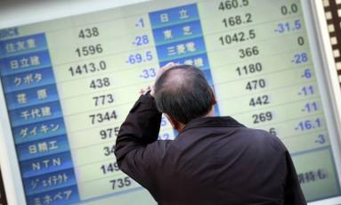 Homem coça a cabeça ao ver o resultado das principais ações do índice Nikkei 225 Foto: Eugene Hoshiko / AP