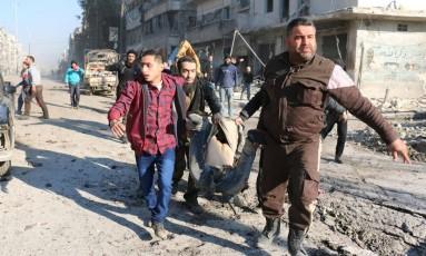 Sírios ajudam ferido em um ataque aéreo do regime de Bashar al Assad na área controlada por rebeldes, em Aleppo Foto: AMEER AL-HALBI / AFP