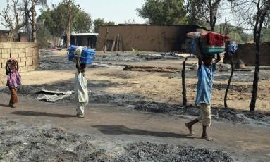 Crianças carregam seus pertences na fuga do grupo extremista Boko Haram em Maiduguri, na Nigéria Foto: STRINGER / AFP