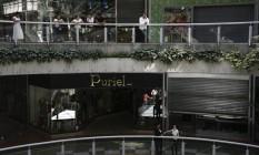 Às escuras. Pessoas esperam do lado lado de fora de lojas fechadas em shopping center de Caracas, após corte no fornecimento de energia elétrica por decisão do governo Foto: MARCO BELLO / Marco Bello/REUTERS