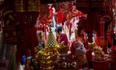 Transição. Cliente observa artigos de decoração para o Ano Novo Chinês: setor de serviço ganha dinamismo, mas pode não ser capaz de absorver trabalhadores demitidos da indústria Foto: Billy H.C. Kwok / Bloomberg
