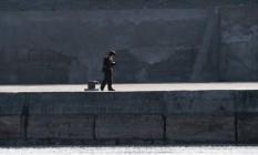Soldado norte-coreano lê livro em região de fronteira com a China, no rio Yalu Foto: JOHANNES EISELE / AFP